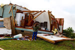 Averie Young surveys the damage to her grandparents' home in Sherman, Texas on Wednesday, April 27, 2016. Terri and Terry Calhoun said they were in bed when high winds tore off their roof and caused major damage to their property.