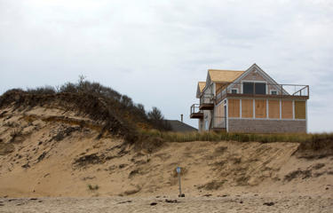 In this photo taken on Saturday, Nov. 7, 2015, the erosion of a dune in front of a house at Ballston beach in Truro, Massachusetts.