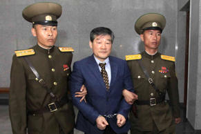 Kim Dong Chul, center, a U.S. citizen detained in North Korea, is escorted to hi...