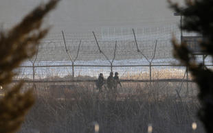 South Korean Army soldiers patrol along the barbed-wire fence in Paju, near the ...