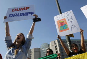 Women hold up signs protesting Donald Trump outside of the Hyatt Regency hotel b...