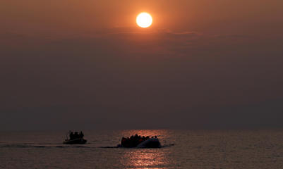 The sun rises as a dinghy carrying refugees and migrants approaches the shores of the Greek island of Lesbos, March 20, 2016.  Alkis Konstantinidis/Reuters