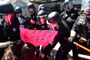 Police in riot gear hold back demonstrators against U.S. Republican presidential candidate Donald Trump outside the Hyatt hotel in Burlingame, Calif., April 29, 2016.