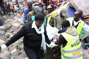 Paramedics evacuate a man rescued from the rubble of a six-storey building that collapsed after days of heavy rain, in Nairobi, Kenya April 30, 2016.