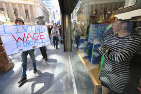 In this file photo, a worker watches from a storefront during a march for immigrant worker rights as part of May Day rallies on May 1, 2013 in New York City.
