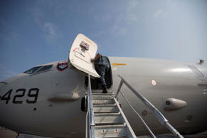 A Navy officer enters United States Navy Boeing P-8 Poseidon at the Singapore Airshow in Singapore, on Monday, Feb. 10, 2014.