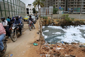 File: Motorists drive over a bridge to cross Bellundur Lake filled with froth from industrial pollution in Bangalore, India, Tuesday, Dec. 1, 2015.