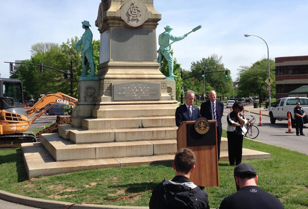 Louisville Mayor Greg Fischer, speaks in front of the Confederate monument near the University of Louisville with university President James Ramsey, in Louisville, Ky., Friday, April 29, 2016. The Confederate monument capped with a statue of Jefferson Davis will be removed from a spot near the University of Louisville campus where it has stood since 1895. (AP Photo/Dylan Lovan)