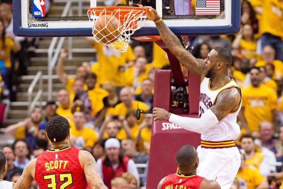 LeBron James #23 of the Cleveland Cavaliers dunks over Mike Scott #32 and Paul Millsap #4 of the Atlanta Hawks during the second half of the NBA Eastern Conference semifinals at Quicken Loans Arena on May 2, 2016 in Cleveland, Ohio. The Cavaliers defeated the Hawks 104-93.
