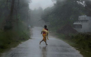 File: A girl runs for shelter in heavy rain brought by Cyclone Phailin in Ichapuram town in Srikakulam district in the southern Indian state of Andhra Pradesh October 12, 2013.