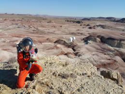 A crew member collecting soil samples with MDRS in the distance.