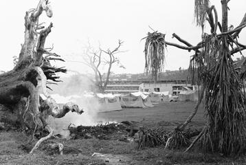 In the capital of the Caribbean nation of Dominica, a rubbish fire smolders between uprooted hulks of trees while, in the background, homeless Dominicans live in a tent camp provided by U.S. aid on Nov. 8, 1979 in Roseau, Dominica. The island was ravaged