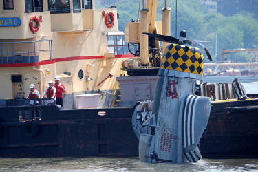 Officials remove a plane out of the Hudson River a day after it crashed, Saturda...