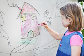 Yong girl drawing a house on a wall