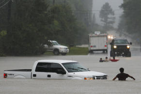 A man, foreground, checks to make sure everyone made it safely out of a truck that flooded when the three men in the background drove around a closed road barrier along Nichols Sawmill Road and lost control of the vehicle in rising flood water Friday, May 27, 2016 in Magnolia, Texas.