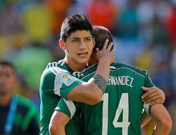 FILE - In a June 29, 2014 file photo, Mexico's Alan Pulido consoles teammate Jav...