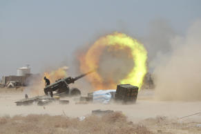 An Iraqi Shi'ite fighter fires artillery during clashes with Islamic State milit...