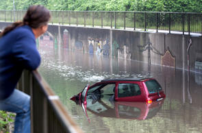 A man looks at a flooded car on a street on May 30, 2016 in Oberhausen after a heavy storm.   At least four people died and several more were injured in the south of Germany after torrential storms caused severe flooding, with a third person also feared