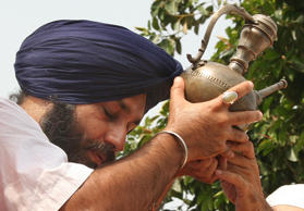 File: Sikh leader Sukhbir Badal pays obeisance to Ganga Sagar one of the personal possession of Sri Gobind Singh, Sikhs tenth Guru, at the India and Pakistan joint border check post of Wagah, India, Sunday, Aug. 27, 2006.