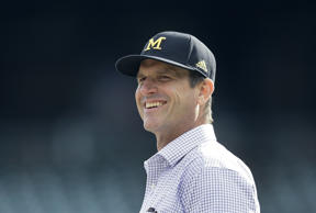 Michigan Wolverines head coach Jim Harbaugh looks on.