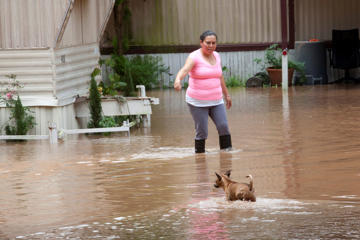 Alejandra Ventura walks through high water as the Brazos River tops its banks and floods a mobile home park in Richmond, Texas, U.S. May 31, 2016.