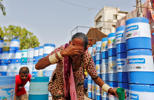 A woman splashes water on her face to cool down at a public water station in Ahmedabad, India May 20, 2016.