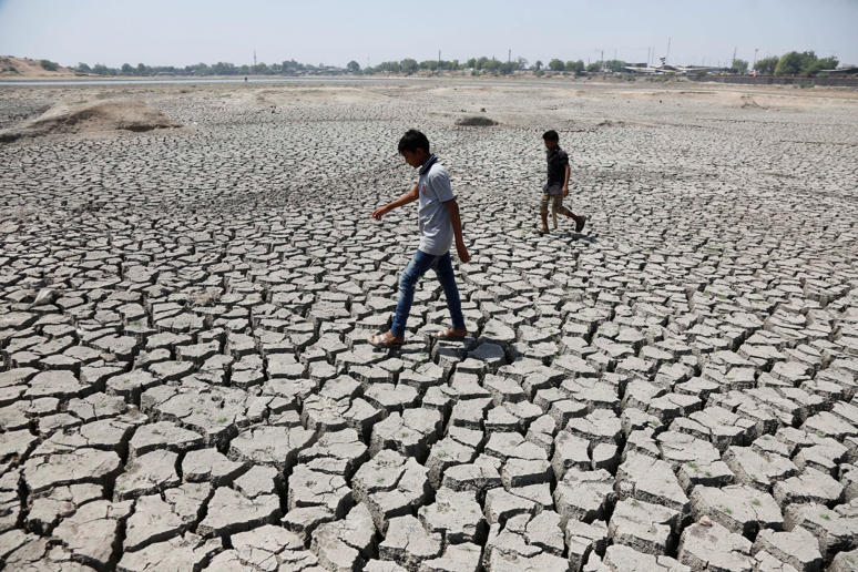 Indian boys on their way to play cricket walk through a dried patch of Chandola Lake in Ahmadabad, India, Saturday, May 14, 2016. Much of India has been suffering from a heat wave for weeks along with a severe drought that has decimated crops, killed liv