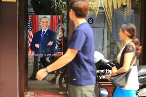 "A Vietnamese couple pass a poster of U.S President Barrack Obama with footnote read ""Welcome to our city"", hanging in a door front in Hanoi, Vietnam on Sunday, May 22, 2016. Obama is expected to land in Hanoi on Monday for a three-day state visit to Viet"