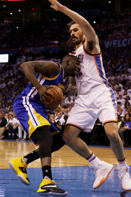 Draymond Green #23 of the Golden State Warriors drives against Steven Adams #12 of the Oklahoma City Thunder