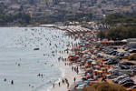 Tourists enjoy the hot weather at Vari beach, some 30 km (19 miles) southeast of Athens July 21, 2013. Foreign tourists are returning to Greece's sun-drenched islands and ancient temples, central bank data showed on Friday, boosting hopes that the key se