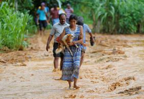 A Sri Lankan landslide survivor caries her dog as she walks on the mud after a landslide