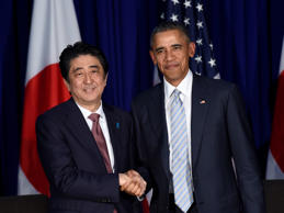 FILE - In this Nov. 19, 2015, file photo, U.S. President Barack Obama, right, and Japan's Prime Minister Shinzo Abe, left, shake hands during a bilateral meeting at the Asia-Pacific Economic Cooperation summit in Manila, Philippines.