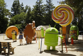 In this Wednesday, May 18, 2016, photo, people pose by Android lawn statues at Google's headquarters in Mountain View, Calif. The tall sculpture, at right, depicts the 2014 version of Android, known as Lollipop. Although a newer version called Marshmallow has been available since October 2015, the bulk of Android phones still have Lollipop or older.