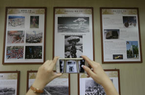 Pictures of the atomic bombings of Hiroshima and Nagasaki and the aftermath catch the attention of a visitor at the Association of Korean Atomic Bomb Victims in Seoul.
