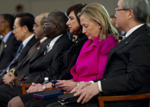 Then-US Secretary of State Hillary Clinton, second from right, checks her Blackberry phone alongside Korean Foreign Minister Kim Sung-hwan, right, as she attends the Fourth High Level Forum on Aid Effectiveness in Busan, Korea, November 30, 2011.