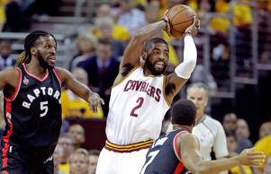 Kyrie Irving, center, of the Cleveland Cavaliers handles the ball in the first quarter against DeMarre Carroll, left, and Kyle Lowry of the Toronto Raptors in game five of the Eastern Conference Finals during the 2016 NBA Playoffs at Quicken Loans Arena on May 25, 2016 in Cleveland, Ohio.