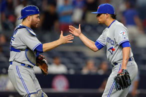 Toronto Blue Jays catcher Russell Martin (55) high fives relief pitcher Roberto Osuna (54) after defeating the New York Yankees at Yankee Stadium. The Blue Jays defeated the Yankees 8-4.