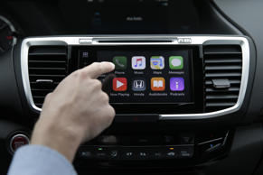 In this Thursday, Aug. 20, 2015, file photo, a person demonstrates Apple CarPlay, which lets drivers use an iPhone and its voice-activated assistant, Siri, to operate some of their vehicle's electronic controls and entertainment systems, in Torrance, California.