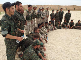 In this photo taken May 21, 2016, members of what the U.S. calls the Syrian Democratic Forces gather after a training session at a firing range in northern Syria. U.S. Gen. Joseph Votel, the head of Central Command, visited the camp to consult with Syrians and talk to US military advisers working with the Syrian fighters.