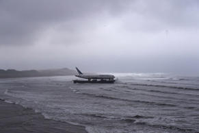 Bad weather surrounds a Boeing 767 airplane as it arrives onto Enniscrone beach after it was tugged from Shannon airport out to sea around the west coast of Ireland, May 7, 2016. It is destined for local funeral director David McGowan's proposed Glamping