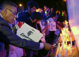People light candles during a candlelight vigil for the victims of EgyptAir flig...