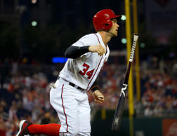 Washington Nationals' Bryce Harper flips his bat as he watches his solo home run...