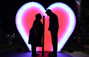 A couple shout 'I love you' as a giant heart-shaped Love-O-Meter is illuminated ...