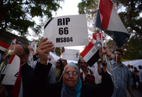An Egyptian woman holds a posters and her national flag as she takes part in a march near the Cairo Opera House in the Egyptian capital on May 26, 2016, for the 66 victims of the EgyptAir MS804 flight that crashed in the Mediterranean Sea.