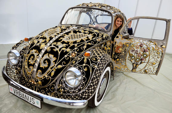 A model sits in a redesigned vintage Volkswagen Beetle by Croatian artist blacksmith Sandro Vrbanus on November 22, 2012 in Essen, western Germany during the Essen Motor Show. The Essen Motor Show runs from December1 to December 9, 2012.  AFP PHOTO / MAR