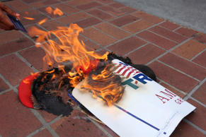 Anti-Trump demonstrators burn Donald Trump's campaign items outside a campaign e...