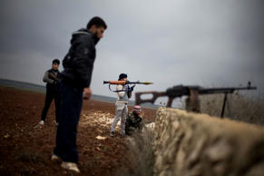 FILE - In this Dec. 10, 2012, file photo, Free Syrian Army fighters take their positions, close to a military base, near Azaz, Syria.