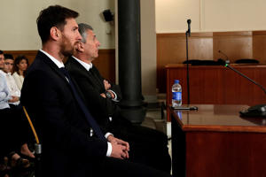 Barcelona's Argentine soccer player Lionel Messi sits in court with his father Jorge Horacio Messi during their trial for tax fraud in Barcelona, Spain.