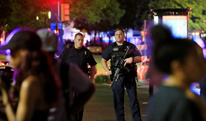 Dallas police and residents stand near the scene where four Dallas police office...