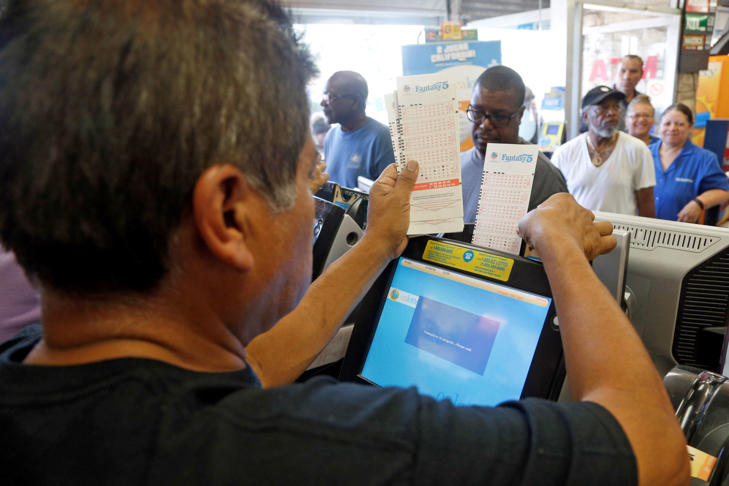 Jesus Vaquez issues lottery tickets at Bluebird Liquors in Hawthorne, Calif., as the Mega Millions lottery had reached $540 million by late Friday afternoon, July 8, 2016.